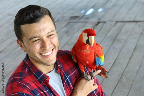 Ethnic man interacting with a gorgeous macaw bird