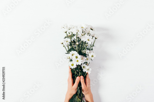 Top view woman's hands holding bouquet of flowers