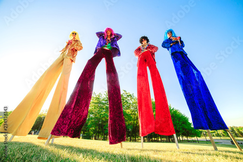 Young people on stilts posing against the blue sky. Fototapeta