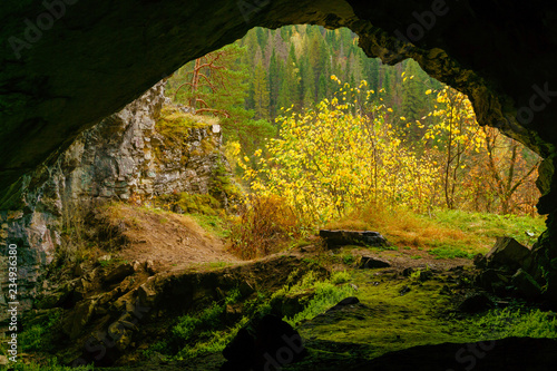 view from the dark natural cave to the bright autumn mountain landscape outside Fototapet