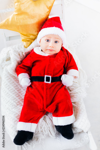 d658be0a7 baby boy in Santa Claus costume lying on a blanket and pillow in ...