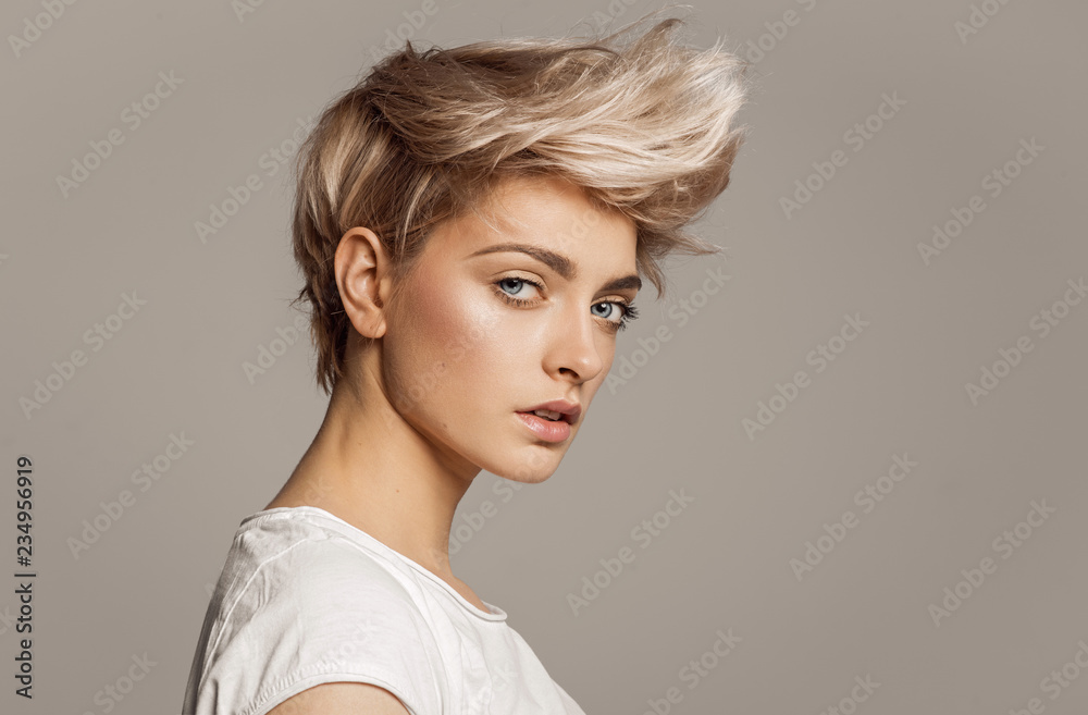 Fototapeta Portrait of young girl with blond fashion hairstyle looking at camera isolated on gray background