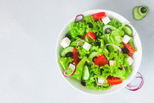 Greek Salad In White Bowl On Grey Light Background With Copy Space - Lettuce, Feta, Tomatoes, Red Onion, Cucmber And Olives, Served With Lemon And Olive Oil
