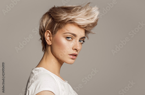 Tuinposter Kapsalon Portrait of young girl with blond fashion hairstyle looking at camera isolated on gray background