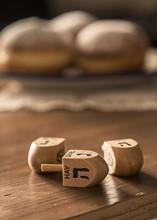 Hanukkah Celebration Concept-dreidels On The Rustic Table With D