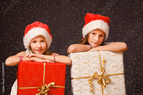 Two young girls, age 8-12 years, wearing Christmas hats, holding Christmas