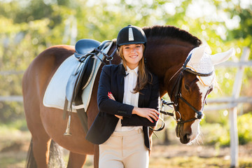 Girl equestrian rider stands near the horse. Horse farm. Horse theme