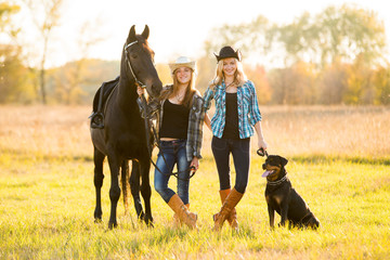 Two girls rider and dog stands near a horse. Horse theme