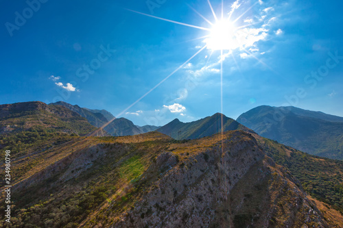 Photo Stands Roe Rocky bare mountains with burnt yellow grass and green trees on the hills in the shade of a bright sun with long rays on a blue clear sky. Summer landscape in Fortress Old Bar Town, Montenegro.
