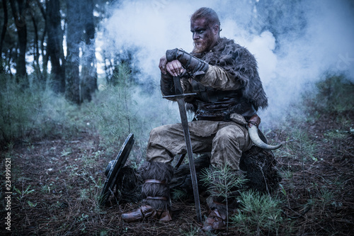 Photo  viking with red beard with armor shield and sword in the battle field