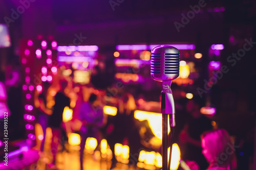 Retro microphone against blur colorful light restaurant background.