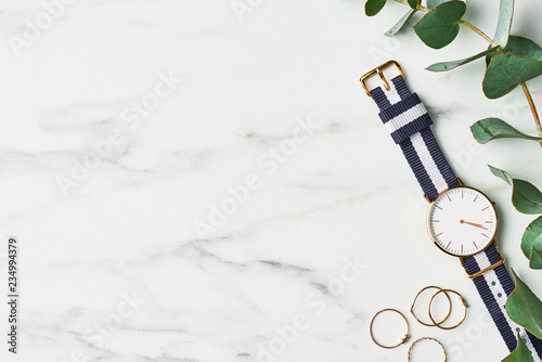 Photo  Women's watch with navy blue and white nylon strap, golden rings and eucalyptus on white marble background
