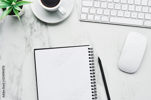 Business composition with white computer keyboard, mouse, coffee cup, artificial plant and notebook with pencil on white marble background. Coffee break at the office concept. Top view with copy space