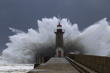 Big storm with big waves near a lighthouse