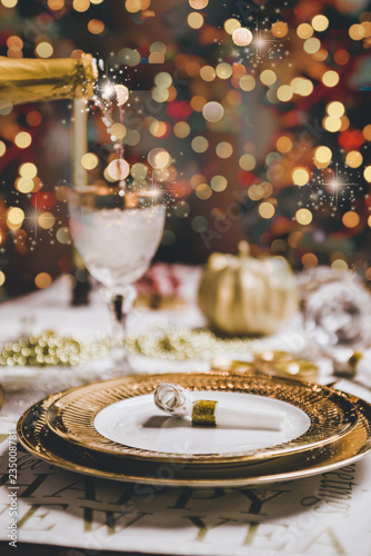 "New year table setting with exclusive and luxury golden cutlery, over a tabletop with celebrations world "" new year"" against a background with great light and bokeh."
