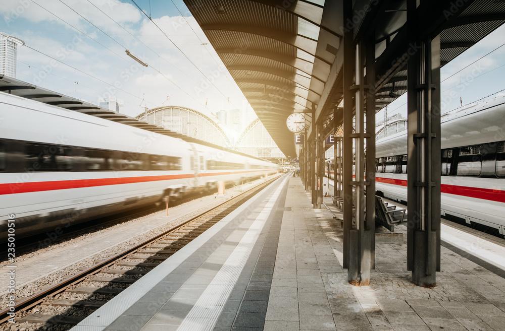 Fototapety, obrazy: Bahn passiert Bahnhof bei blauem Himmel