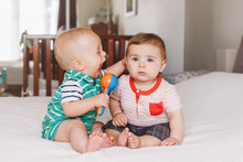 Group Portrait Of Two White Caucasian Cute Adorable Funny Baby Boys Sitting Together On Bed Communicating And Playing. Friendship Childhood Concept. Best Friends Forever. Children Fighting Screaming