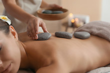 Beautiful Young Woman Getting Hot Stone Massage In Spa Salon