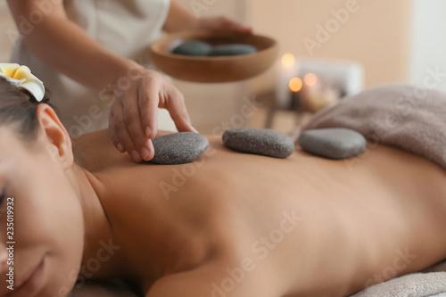 Beautiful young woman getting hot stone massage in spa salon Fototapete