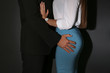 Boss molesting his female secretary on dark background. Sexual harassment at work