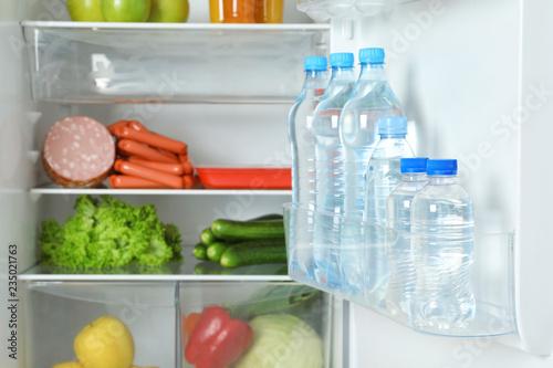 Bottles of water on refrigerator door shelf, closeup
