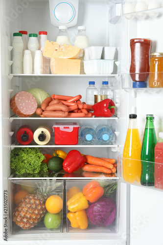 Open refrigerator with many different products, closeup