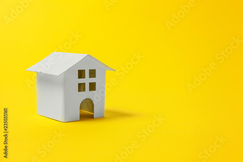 Foto  Simply design with miniature white toy house isolated on yellow colourful trendy modern fashion background