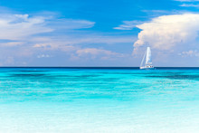 A White Sailboat Parked At The Beach, Turquoise Waters And Beautiful White Sand.