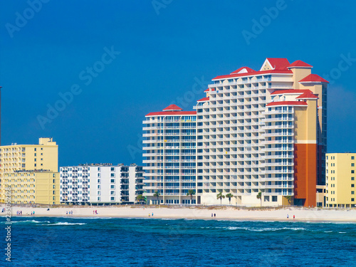 Fotografie, Obraz Condos and hotels on the shore of the Gulf of Mexico at Orange Beach, Alabama on a hazy day