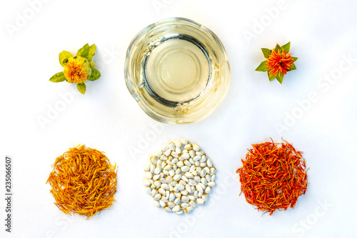 Yellow, red dried petals, inflorescences, seeds and oil of safflower against a white background. View from above. Flat lay.