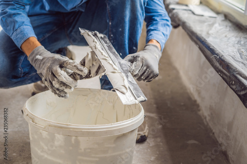 Carta da parati master is applying white putty on a wall and smearing by putty knife in a room o
