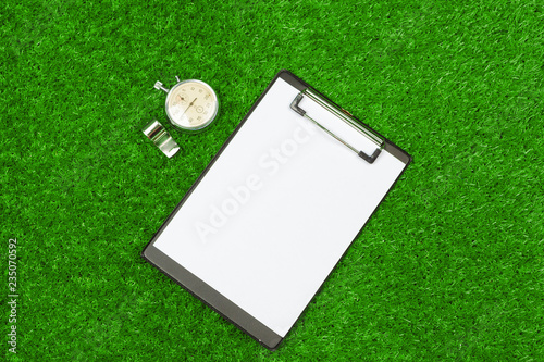 Sheet of paper and sports equipment on grass close-up Wallpaper Mural