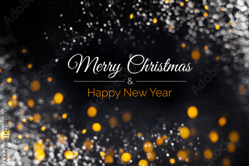 Fotografía  Merry Christmas and Happy New Year card with text, yellow and white lights soft focus on black background