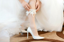 In The Morning, The Bride In Stockings And A White Wedding Dress In White Heel Shoes Wears A Garter On Her Leg, The Bride Is Holding Her Hands For The Garter
