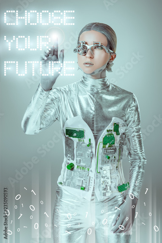 """Photo  young cyborg touching """"choose your future"""" lettering on grey with digital data,"""