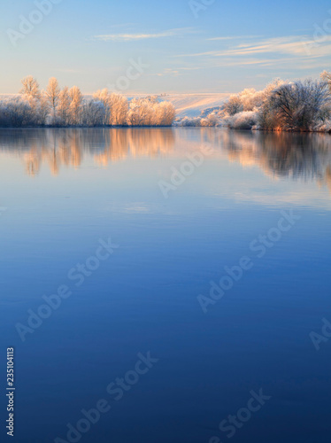 Winter Landscape Reflecting in River at Sunrise, Trees covered by hoarfrost and snow, blue sky