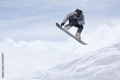 Snowboarder flying on the background of snowy slope Tablou Canvas