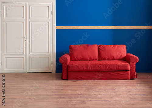 Dark blue wall and wooden banner on the wall, red sofa with ...