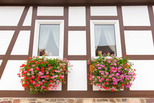 Facade Of Half-timbered House With Geranium Flowers