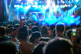 Concert crowd of Music fanclub hand holding mobile smart phone taking video record or Live stream with super star songer, musical and concert concept