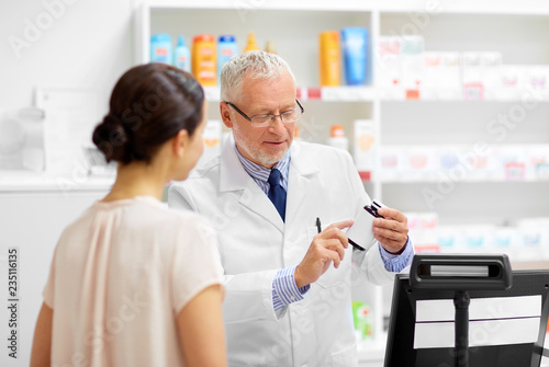 Poster Pharmacie medicine, pharmaceutics, healthcare and people concept - senior apothecary with drug and female customer at pharmacy