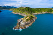 Aerial drone view of a rocky peninsula and a calm, tropical ocean