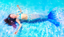 Young Mermaid Floating In Pool With Eyes Closed