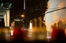 (selective Focus) Broadway Sign Illuminated At Night In Manhattan, New York. Steam Coming Out Of The Manhole On The Right Side.