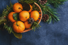 Tangerines In A Wooden Basket And Pine Cones And Branches For Christmas Decoration. View Top, Flat Lay