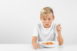 little blond boy in front of white background eats spaghetti with both hands and smiles