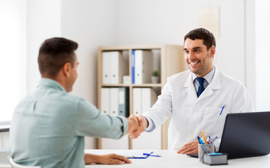 Fototapeta medicine, healthcare and people concept - smiling doctor and male patient shaking hands at hospital