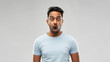 emotion, expression and people concept - shocked or scared man in t-shirt over grey background