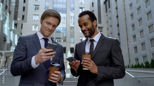 Photo  Coworkers having coffee break, showing photos from vacation on phone, social net