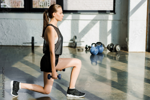 attractive athletic sportswoman doing lunge exercise with dumbbells at fitness c Fototapet